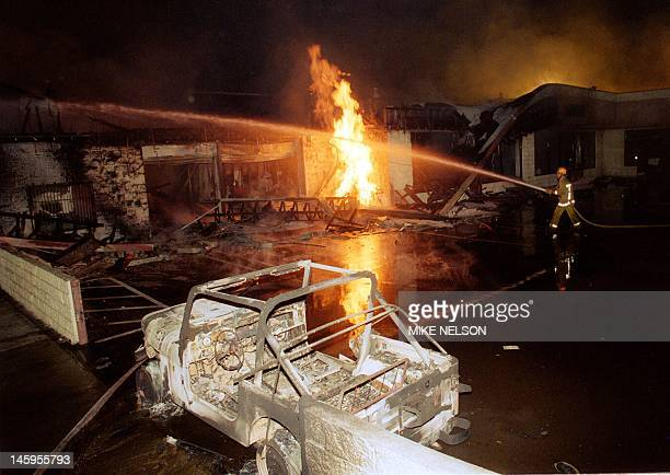 A fireman sprays water on a burning auto parts store in Los Angeles 30 April 1992 Riots broke out in Los Angeles 29 April 1992 after a jury acquitted...