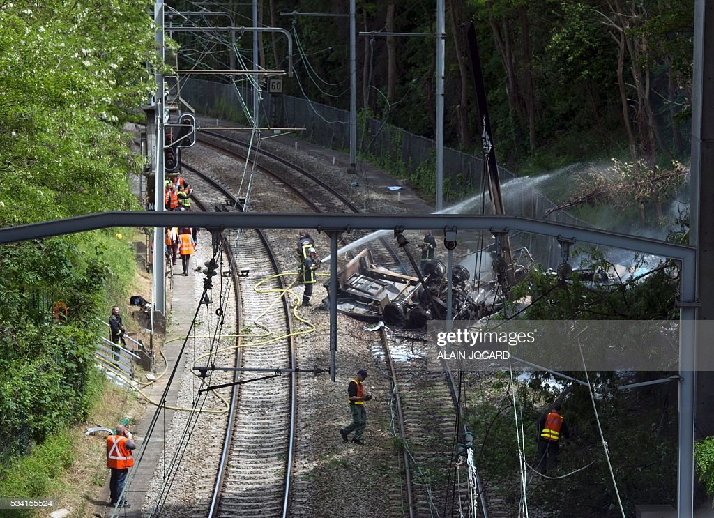 A fireman sprays water on a truck accidentally fallen on the RER B suburban railway from an highway bridge, in Palaiseau near Paris on May 25, 2016. / AFP / ALAIN