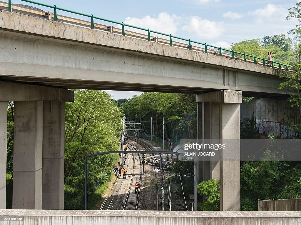 A fireman sprays water on a truck accidentally fallen on the RER B suburban railway from an highway bridge, in Palaiseau near Paris on May 25, 2016. / AFP / ALAIN