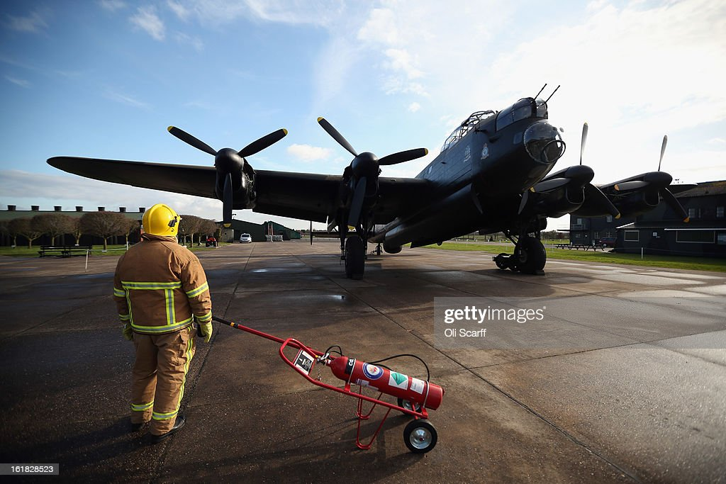 A fireman stands by as engine tests are carried out on the Lancaster bomber 'Just Jane', which is being restored with the aim of getting it airworthy, at Lincolnshire Aviation Heritage Centre on February 14, 2013 in East Kirkby, England. The plane, which last flew in 1971, would become one of only three airworthy Lancaster bombers in the world. Brothers Fred and Harold Panton, owners of the Lincolnshire Aviation Heritage Centre, are restoring the plane in memory of their sibling, Christopher Panton, who died aged 19 when his Lancaster was shot down in 1944.
