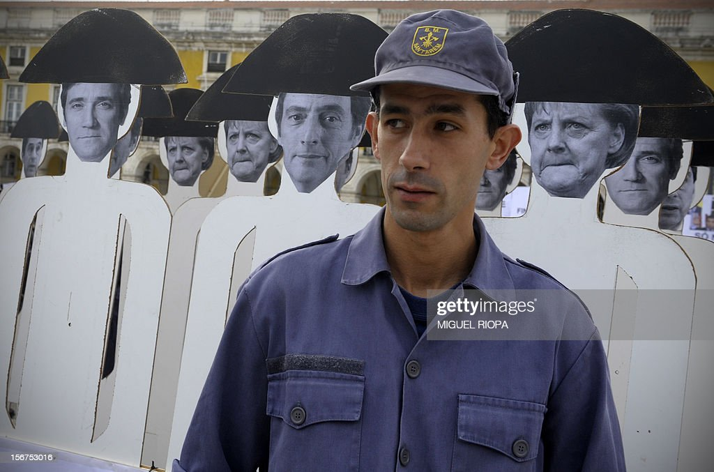 A fireman stands in front of dolls depecting EU leaders during a demonstration against the govenrment's austerity measures at Comercio Square in Lisbon, on November 20, 2012. The government aims to save 4.0 billion euros via state reform measures, but its austerity budgets have led to howls of protest from civil servants and trade unions in particular. AFP PHOTO/ MIGUEL RIOPA