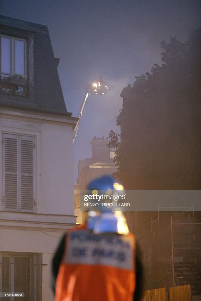 A fireman stands near the 17 century Hotel Lambert during a fire on July 10, 2013 in Paris. Hotel Lambert, by the architect Louis Le Vau located at the tip of the Ile Saint-Louis in Paris, was purchased in 2007 by the brother of the Emir of Qatar and currently being restore. AFP PHOTO / KENZO TRIBOUILLARD