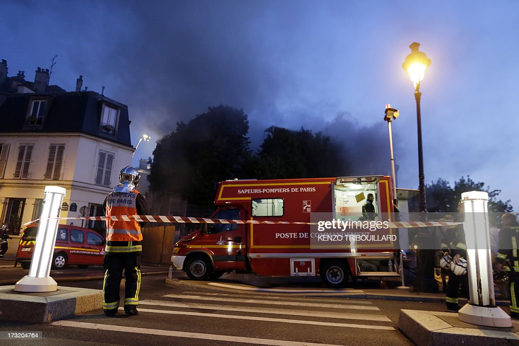 A fireman stands near the 17th-century Hotel Lambert during a fire on July 10, 2013 in Paris. Hotel Lambert, by the architect Louis Le Vau located at the tip of the Ile Saint-Louis in Paris, was purchased in 2007 by the brother of the Emir of Qatar and currently being restore. AFP PHOTO / KENZO TRIBOUILLARD