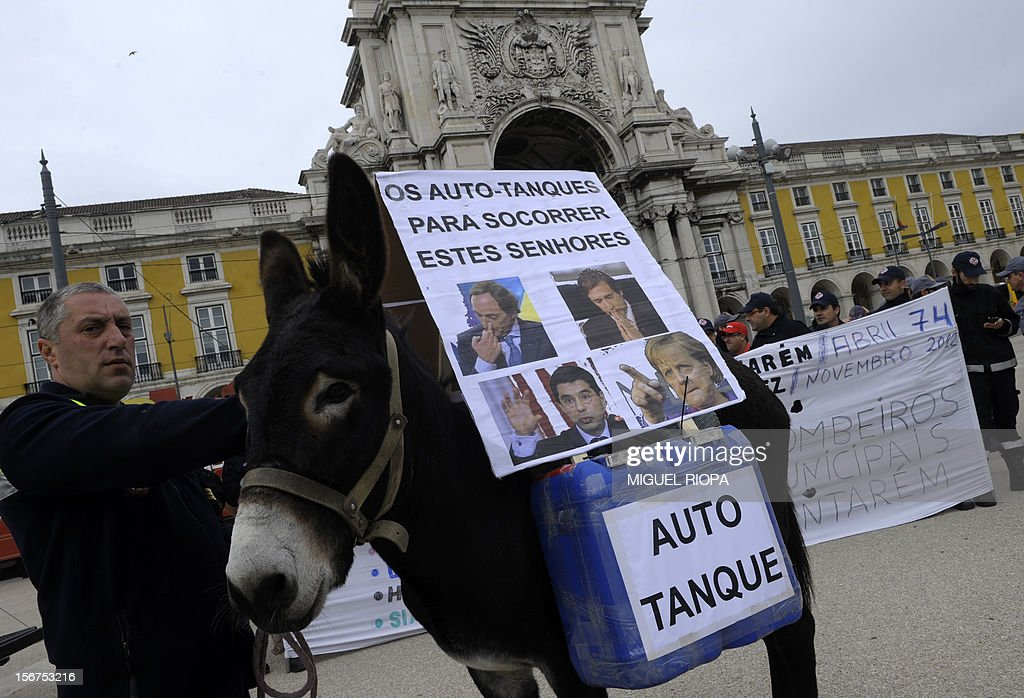 A fireman stands next to a donkey carrying a placard reading 'Our fire engines to save these men' and depecting pictures of Portugal's Finance Minister Vitor Gaspar and German Chancellor Angela Merkel during a demonstration against the govenrment's austerity measures at Comercio Square in Lisbon, on November 20, 2012. The government aims to save 4.0 billion euros via state reform measures, but its austerity budgets have led to howls of protest from civil servants and trade unions in particular. AFP PHOTO/ MIGUEL RIOPA