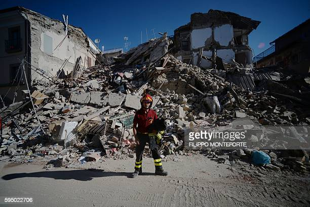 TOPSHOT A fireman stands next to ruins in the central destroyed street of Amatrice in central Italy on August 25 2016 after a strong eartquake that...