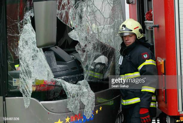 A fireman stands next to the smashed front windshield of a tour bus that crashed into a concrete bridge support on the A10 highway on September 26...