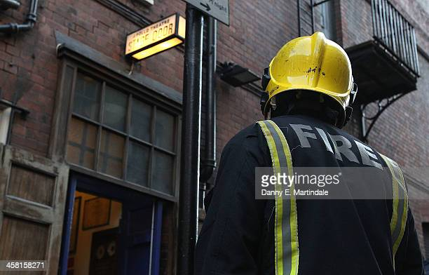 A fireman stands outside the stage door fo the Apollo Theatre following the partial collapse of the theatre's roof last night on December 20 2013 in...