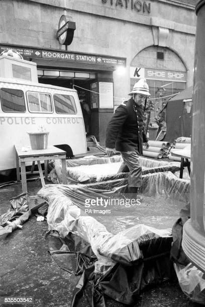 A fireman stepping through antiseptic tanks after working in the tunnel at Moorgate Underground Station where rescuers are still trying to recover...