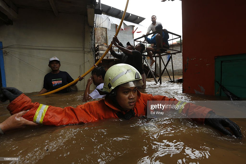 A fireman struggles through the rapid current caused by floodwaters in the RawaJati area on January 18, 2013 in Jakarta, Indonesia. According to the National Disaster Management Agency, about 50 percent of the capital is under water following the floods which have so far claimed eleven lives and displaced thousands of Indonesians.