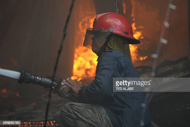 A fireman trains his hose on a burning house after a fire gutted a shanty town near a jail building in Manila on December 4 2015 Hundreds of inmates...