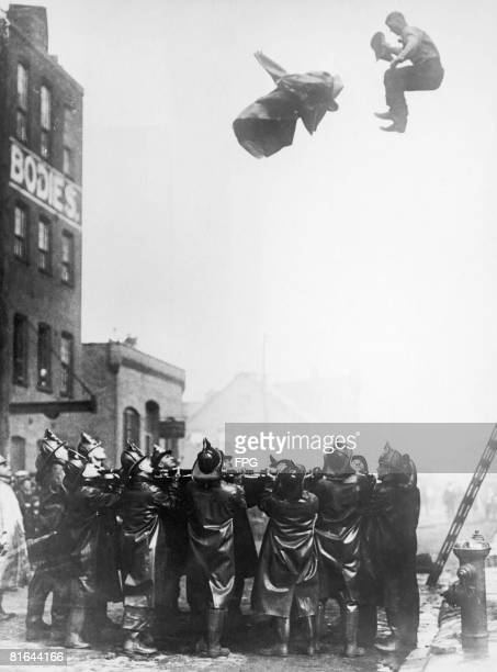 A fireman trapped in the upper floor of a burning building leaps onto a safety net held by his colleagues in Newark New Jersey circa 1925 He has...