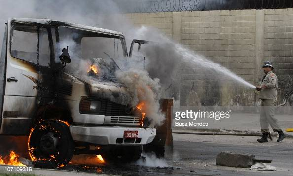 A fireman tries to control the flames in a truck which has been set fire by members of the criminal organizations ADA and Comando Vermelho at...