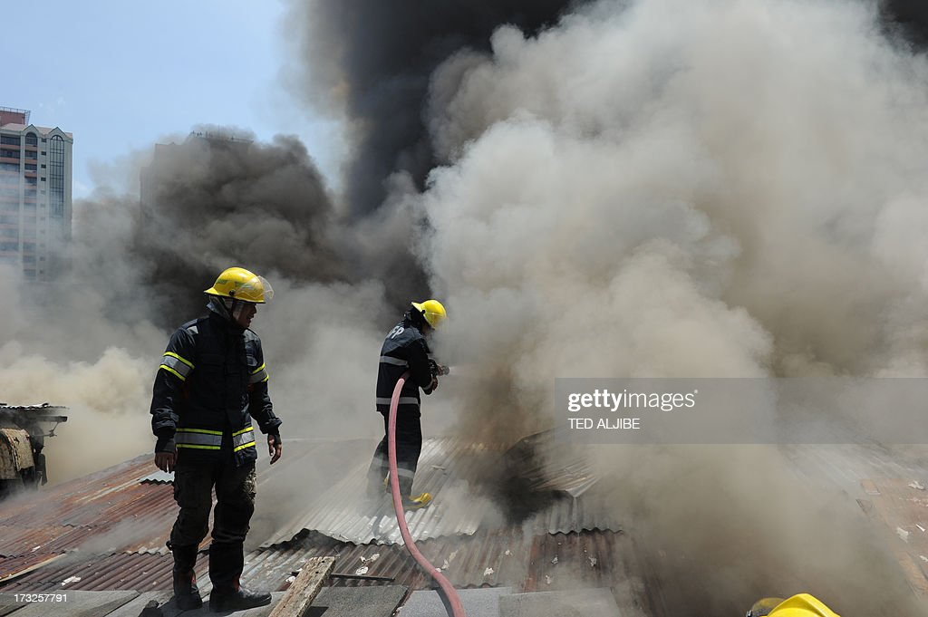 A fireman tries to put out a fire after a blaze engulfed a shanty town at the financial district of Manila on July 11, 2013. There were no immediate reports of casualties from the blaze, which occurred mid-morning amid government plans to relocate thousands of families living in areas vulnerable to floods and typhoons.