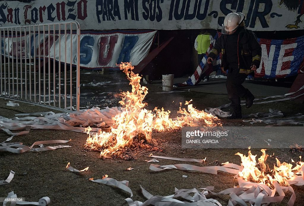 A fireman tries to stop the fire on paper ribbon at Pedro Bidegain stadium in Buenos Aires, Argentina, on August 13, 2014 during the Copa Libertadores 2014 final second leg football match between San Lorenzo and Nacional. San Lorenzo defeated Paraguay's Nacional 1-0 and is the new Copa Libertadores champion. AFP PHOTO / DANIEL GARCIA