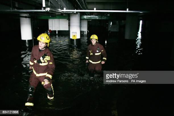 Fireman wade through water in Kendall Street Car Park after a water main burst in Edgware Road London