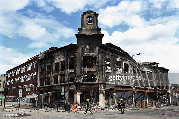 Fireman walk past the smouldering remains of a burnt out building after riots on Tottenham High Road on August 7 2011 in London England Rioting broke...