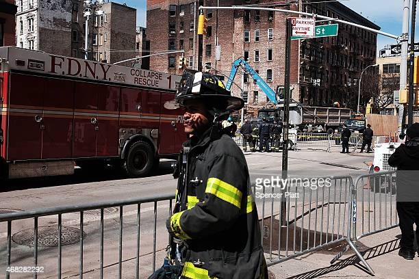 A fireman walks along 2nd avenue as part of it remains closed near the scene where three buildings collapsed and killed two men in the East Village...