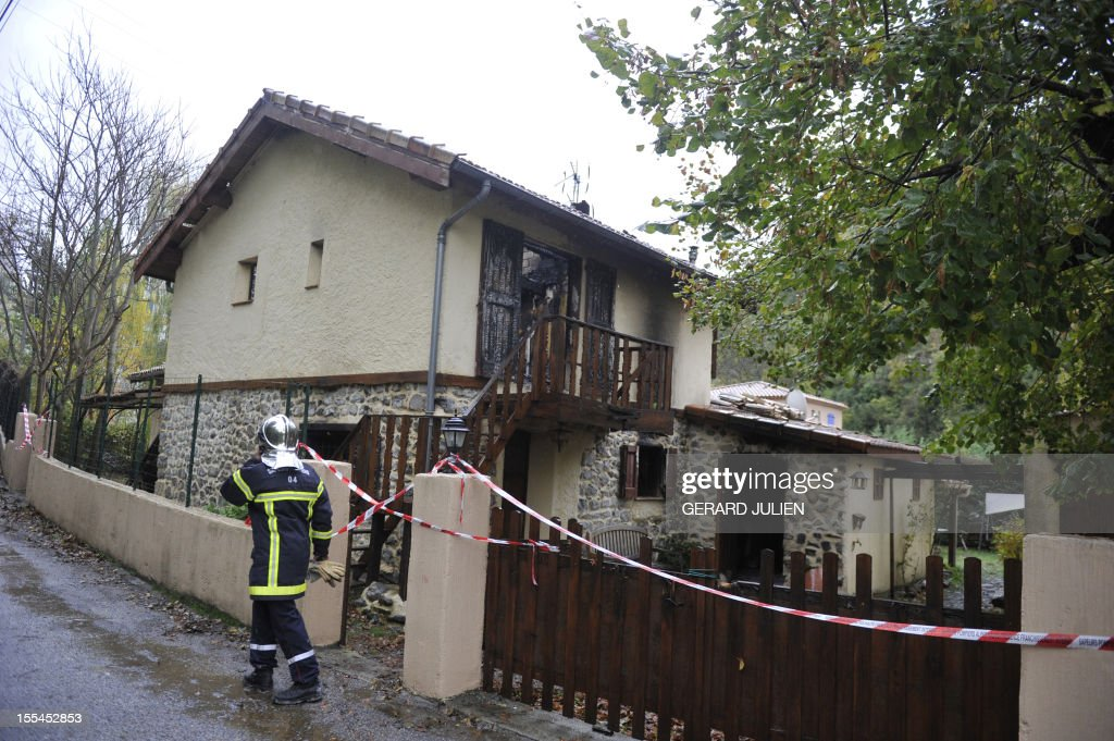 A fireman walks in front of a burned house where two volunteer firefighters, including a 16 year-old man, died while trying to extinguish the fire in Digne-les-Bains, southeastern France, on November 4, 2012. AFP PHOTO GERARD JULIEN