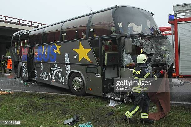 A fireman walks next to the smashed front windshield of a tour bus that crashed into a concrete bridge support on the A10 highway on September 26...