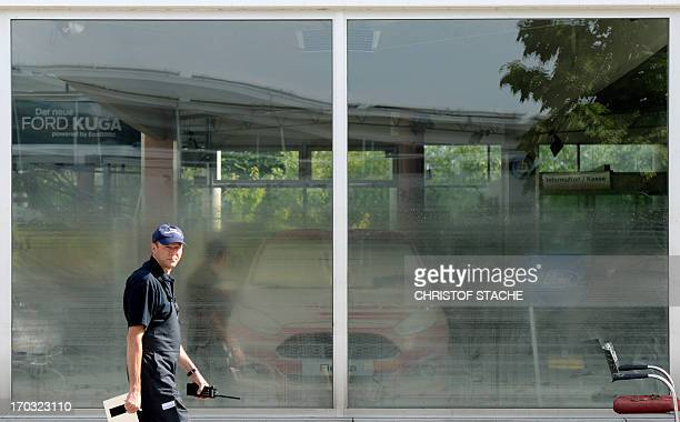 A fireman walks past the shop window of a car dealer hit by floodwaters of the river Danube in Fischerdorf near Deggendorf southern Germany on June...