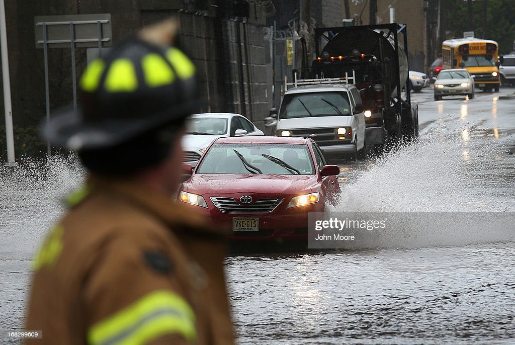 A fireman watches as traffic moves through floodwaters on May 8, 2013 in Jersey City, New Jersey. Heavy rains flooded streets, stranding some motorists during morning rush hour traffic.