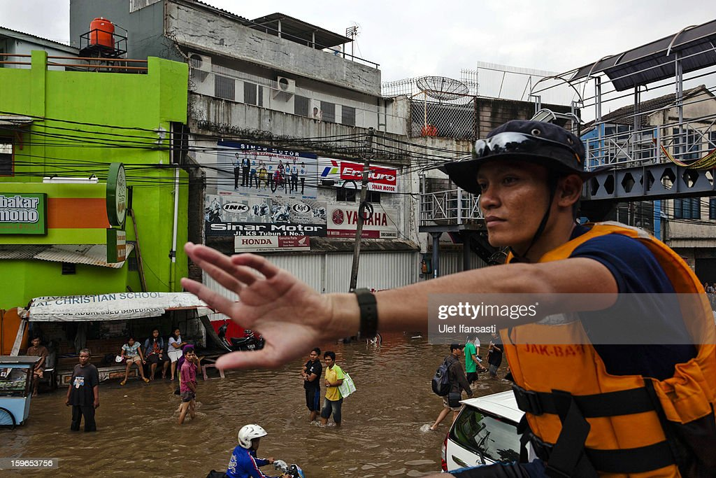A fireman watching people walking through floodwaters in Central Jakarta district on January 18, 2013 in Jakarta, Indonesia. According to the National Disaster Management Agency, about 50 percent of the capital is under water following the floods which have so far claimed eleven lives and displaced thousands of Indonesians.