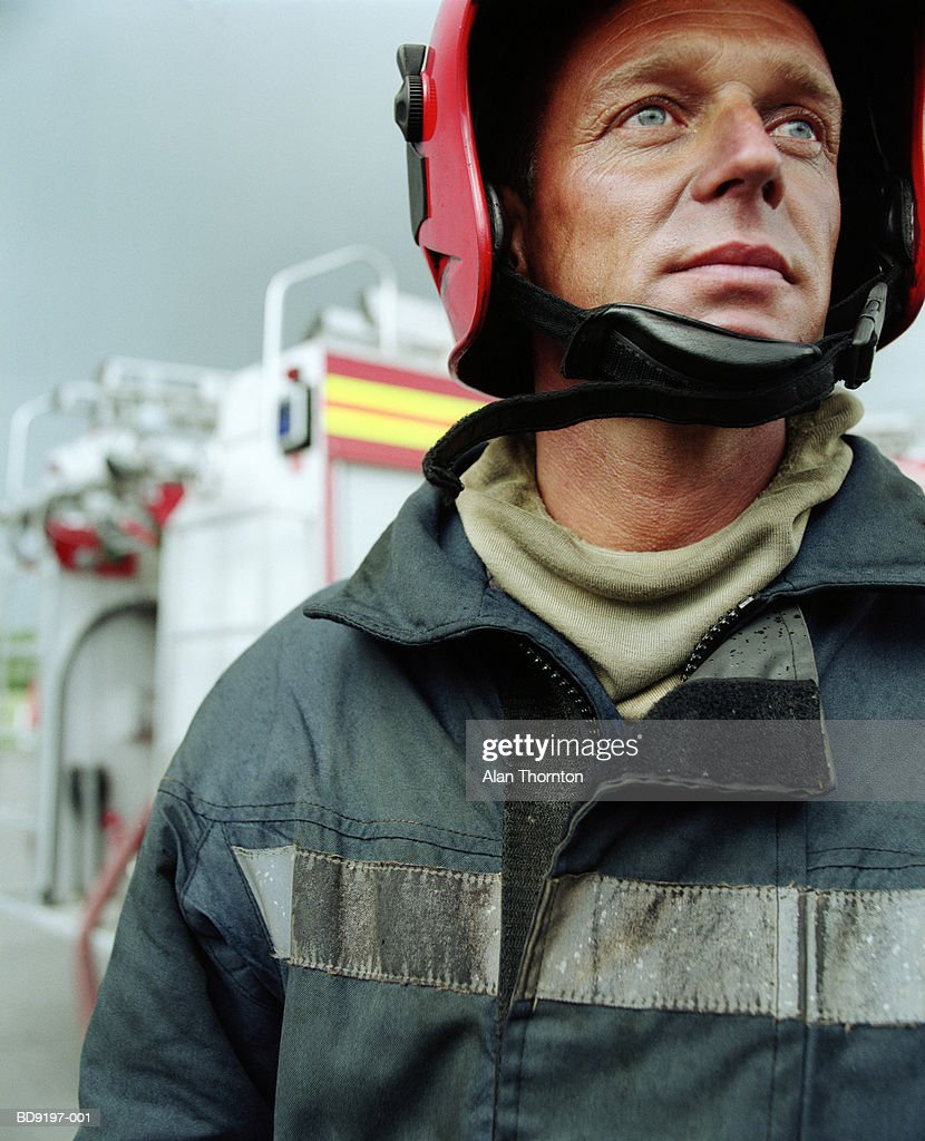 Fireman wearing safety helmet, close-up : Stock Photo