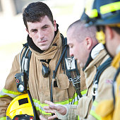 Fireman with Gear On Listening to Fellow Firefighter Talking