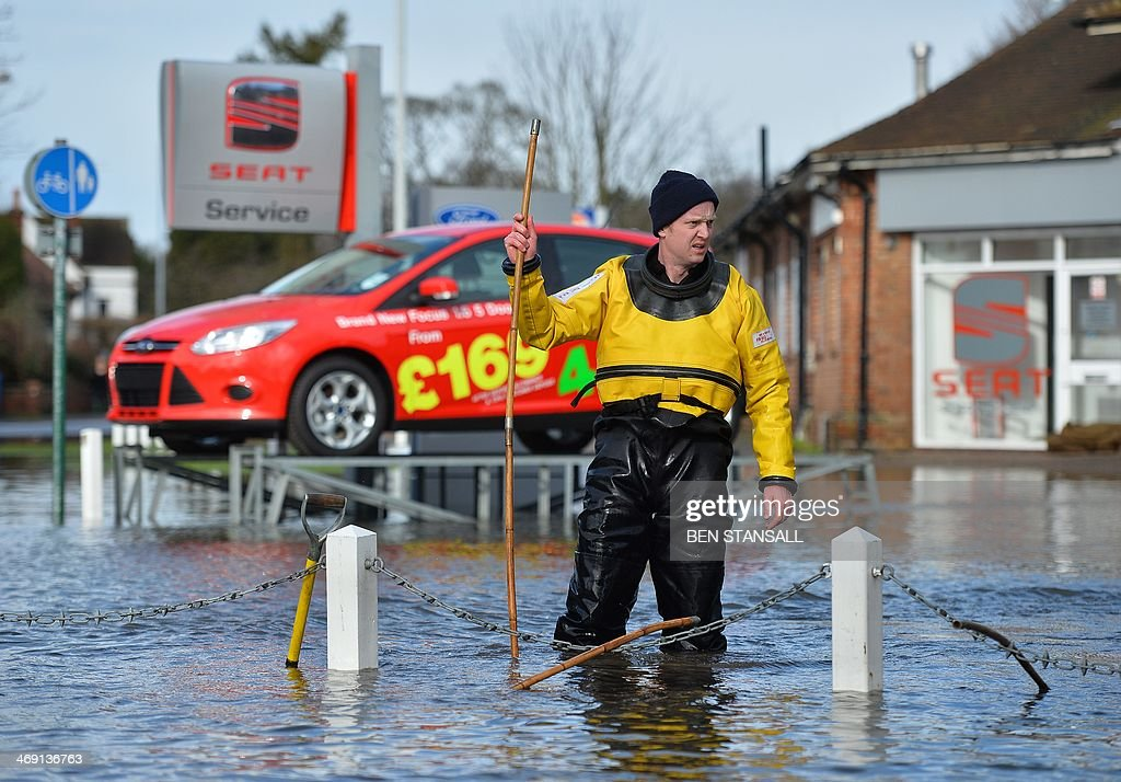 A fireman works to clear drains in the flooded streets of Datchet, west of London, on February 13, 2014. Hurricane-force winds from an Atlantic storm left tens of thousands of Britons without power Thursday and one man dead, adding to the misery after devastating floods caused by the wettest winter in 250 years.
