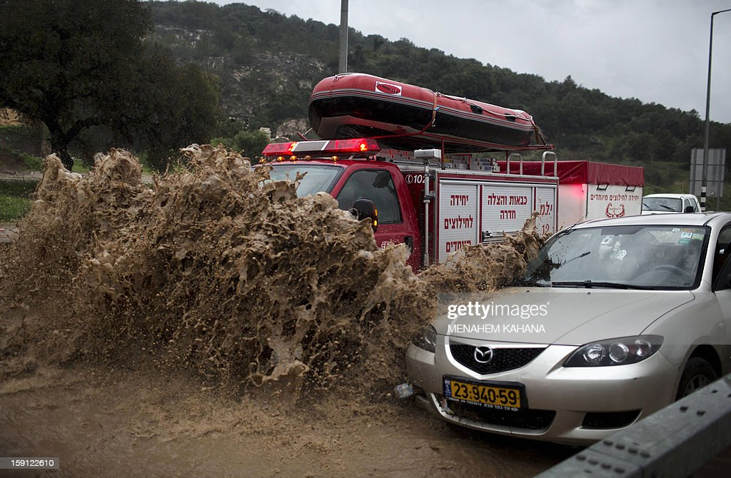 A fireman's truck drives through a flooded road to rescue people trapped in their vehicles near the Israeli-Arab town of Kfar Qara, in central Israel, on January 8, 2013. Stormy weather, including high winds and heavy rainfall, lashed Israel and the Palestinian territories, downing powerlines and trees and blocking roads causing several injuries.