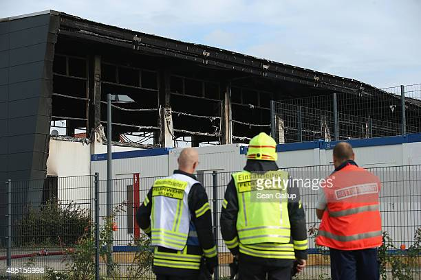 Firemen and an emergency services worker stand outside a sports hall struck by fire that was intended to house refugees and migrants applying for...