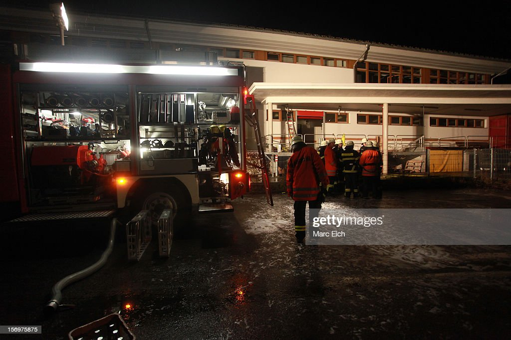 Firemen and emergency rescue crews stand outside a Caritas employment facility for the handicapped in which 14 people died in a fire on November 26, 2012 in Titisee-Neustadt, Germany. The fire was reportedly caused by an explosion at the facility, where approximately 120 people with disabilities are employed in light manufacturing.