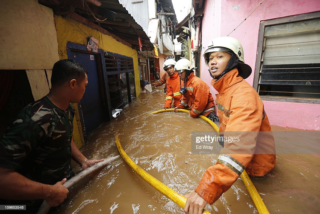 Firemen and neighborhood residents move firehoses into position to put out a fire that engulfed several houses in a flooded are on January 18, 2013 in Jakarta, Indonesia. According to the National Disaster Management Agency, about 50 percent of the capital is under water following the floods which have so far claimed eleven lives and displaced thousands of Indonesians,