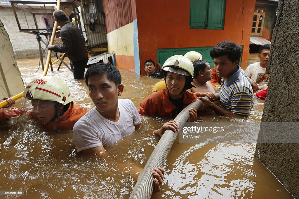 Firemen and neighborhood residents move firehoses into position to put out a fire that engulfed several houses in a flooded area on January 18, 2013 in Jakarta, Indonesia. According to the National Disaster Management Agency, about 50 percent of the capital is under water following the floods which have so far claimed eleven lives and displaced thousands of Indonesians.
