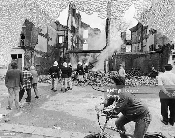 Firemen and onlookers beside a burntout building on the second day of riots in Brixton South London 13th April 1981
