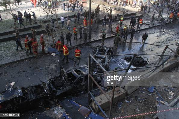 Firemen and onlookers gather around burnt cars at the scene of a huge blast that rocked central Beirut on December 27 killing an adviser to former...