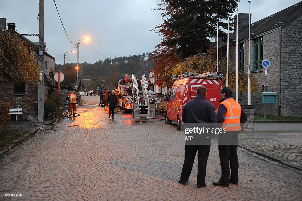 Firemen and police officers are pictured on the site of a fire that killed four people in a house in the rue des Grottes street in Han-sur-Lesse on November 12, 2012. Belgium Out
