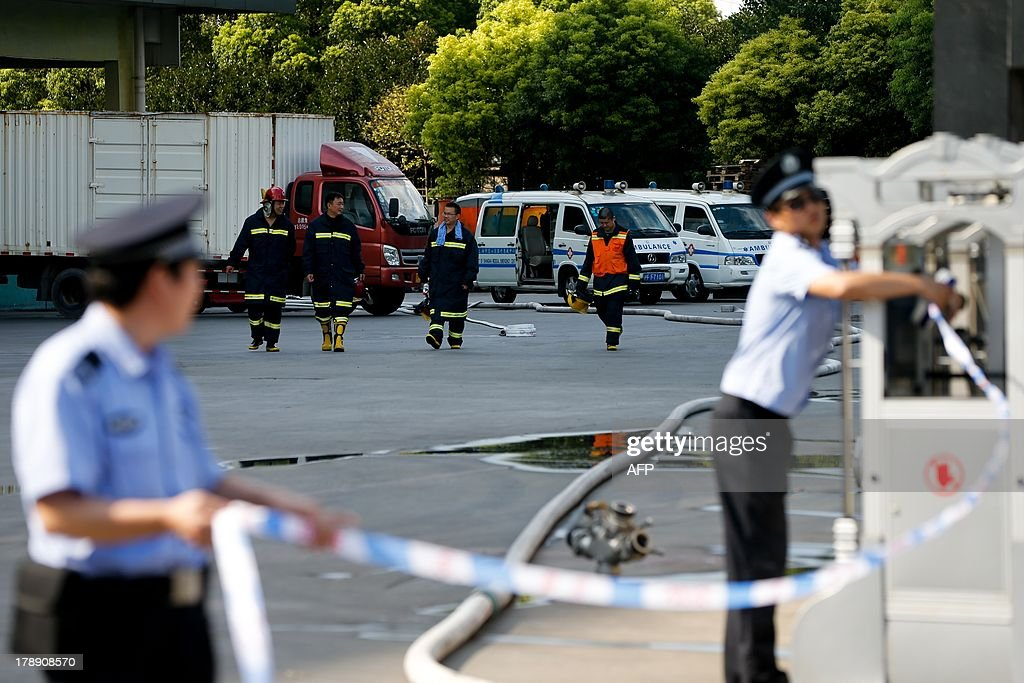 Firemen and police work near a cold storage unit following an ammonia leak in Baoshan district of Shanghai on August 31, 2013. An ammonia leak from a cold storage unit at a food company in China's commercial hub of Shanghai killed 15 people on August 31 and sickened dozens, the city government said. CHINA OUT AFP PHOTO