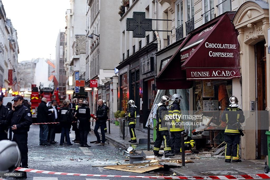 Firemen (R) and policemen gather for rescuing operations at the site of a blast that occurred at a chocolate shop in the Paris 9th district, on February 14, 2014. Five people were injured, one seriously, on February 14, 2014 in an explosion at a construction site in a chocolate shop in Paris. The wounded are all workers who were working on the site. AFP PHOTO / FRANCOIS GUILLOT