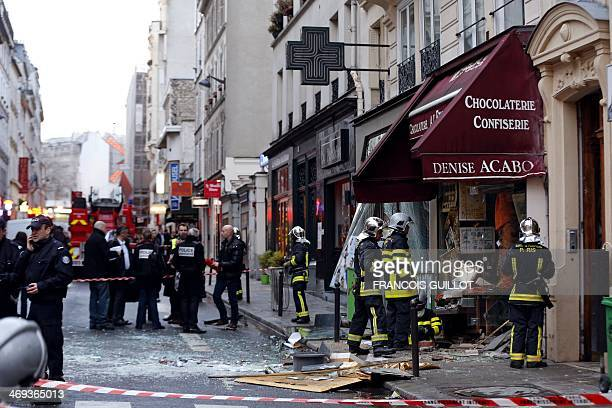 Firemen and policemen gather for rescuing operations at the site of a blast that occurred at a chocolate shop in the Paris 9th district on February...