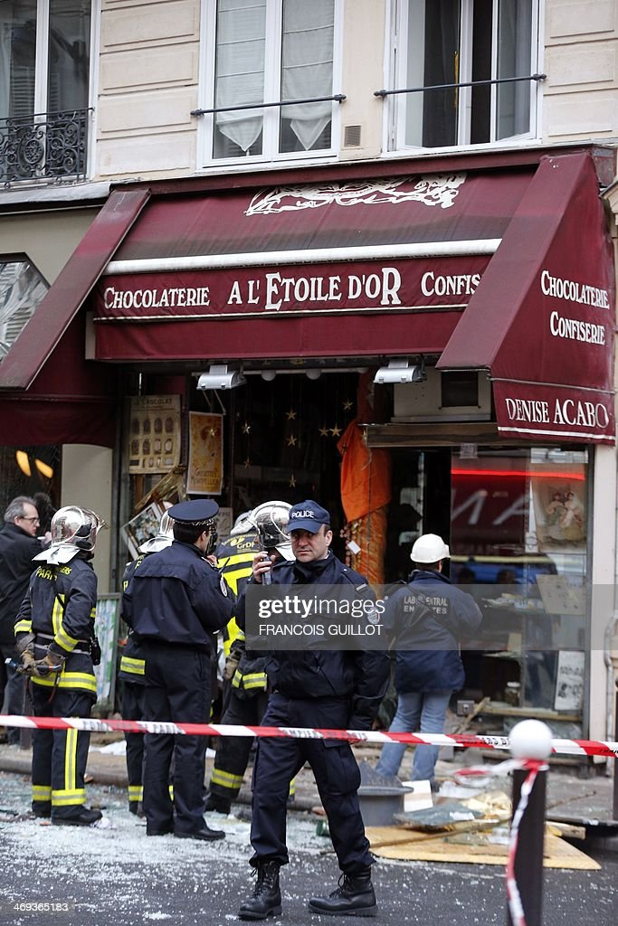 Firemen (R) and policemen gather for rescuing operations at the site of a blast that occurred at chocolate shop 'A l'Etoile d'Or' in the Paris 9th district, on February 14, 2014. Five people were injured, one seriously, on February 14, 2014 in an explosion at a construction site in a chocolate shop in Paris. The wounded are all workers who were working on the site.