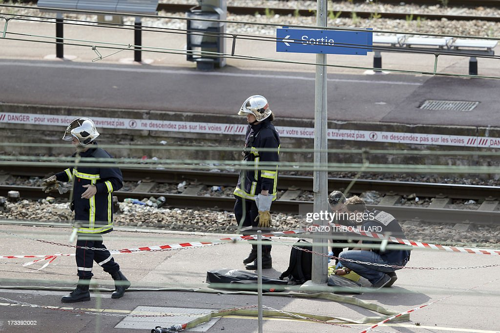 Firemen and policemen work on the site of a train accident on July 13, 2013 at the railway station of Bretigny-sur-Orge, near Paris. At least six people were killed and dozens injured yesterday after a speeding train derailed at a station in the southern suburbs of Paris, officials said.