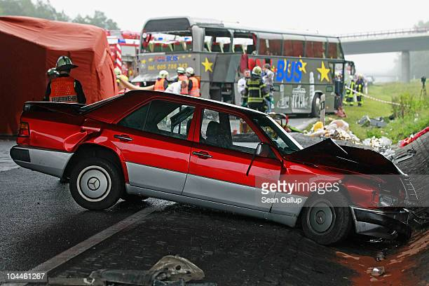 Firemen and rescue workers stand around a smashed Mercedes car and a tour bus that crashed into a concrete bridge support on the A10 highway on...