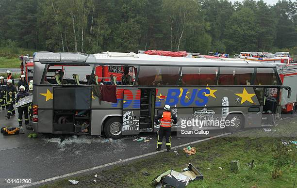Firemen and rescue workers stand around a tour bus that crashed into a concrete bridge support on the A10 highway on September 26 2010 near Berlin...