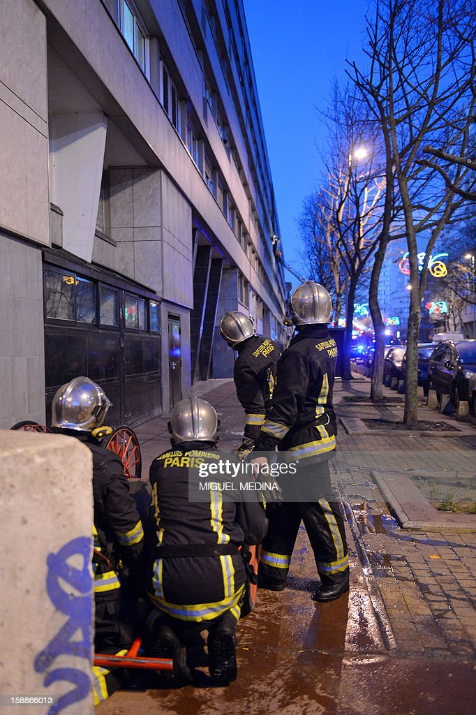 Firemen are at work near an apartment block where a fire broke out, killing at least five of its residents, on January 2, 2013 in Genneviliers, outside Paris.