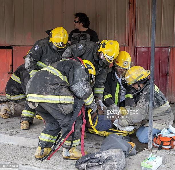 Firemen assist a man who was swept the current after heavy rainfall caused the overflowing of the Copiapo river and the flooding of parts of the city...