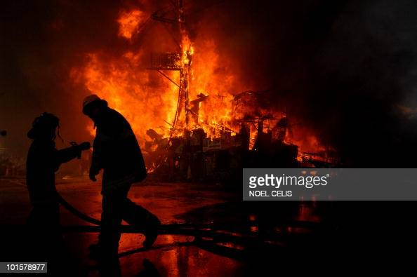 Firemen battle to control a fire raging through a shanty residential area in Quezon City in suburban Manila on April 25 2010 The fire gutted hundreds...