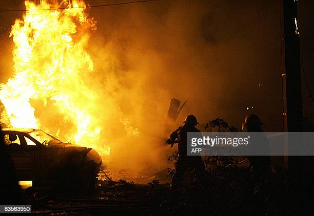 A firemen battles a car on fire after an aircraft crashed and burst into flames in Mexico City on November 4 2008 At least three people died...