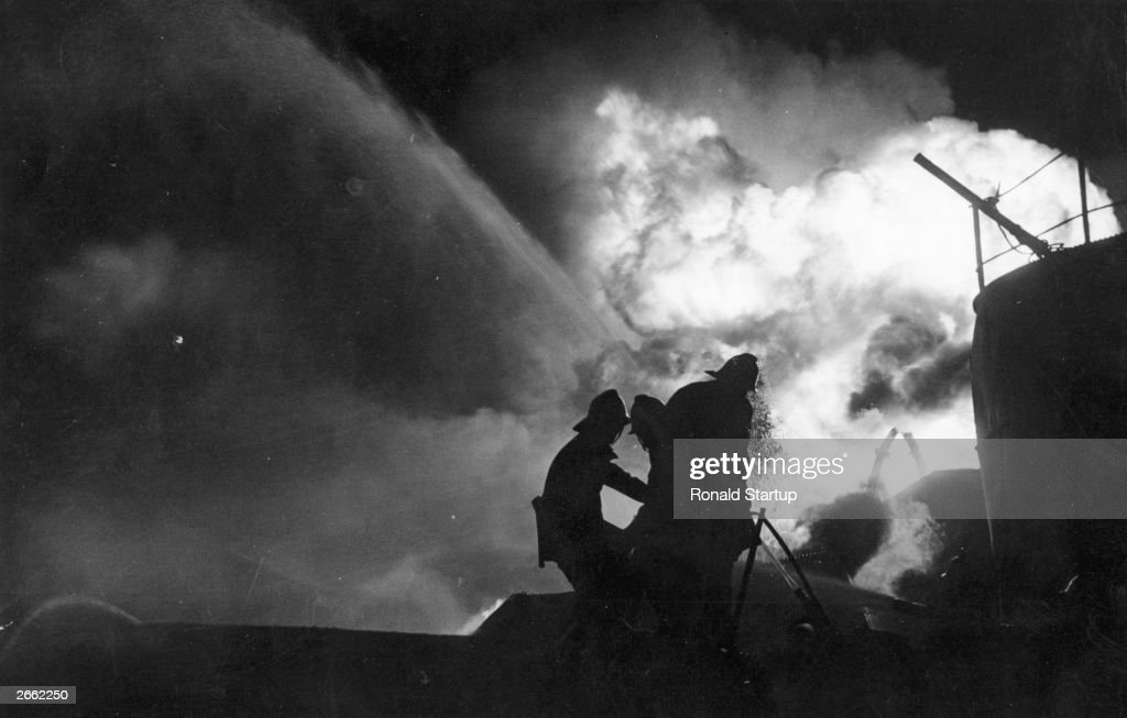 Firemen battling frantically across a chasm of flaming oil to try and isolate a threatened storage tanker in Avonmouth, Bristol, UK. Original Publication: Picture Post - 5582 - Inferno At Avonmouth - pub. 1951