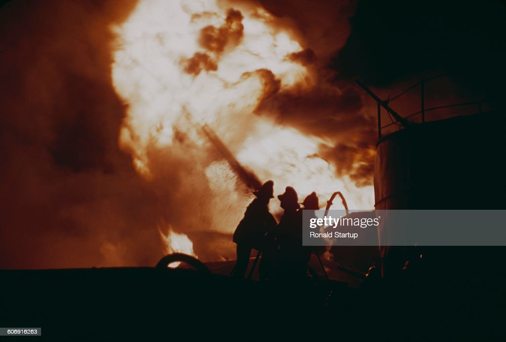 Firemen battling frantically across a chasm of flaming oil to try and isolate a threatened storage tanker in Avonmouth Bristol UK 10th November 1951...